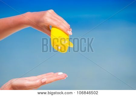 Closeup suncream bottle background blue ocean and sky
