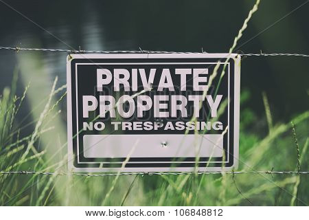 Fence property line with a no trespassing sign posted
