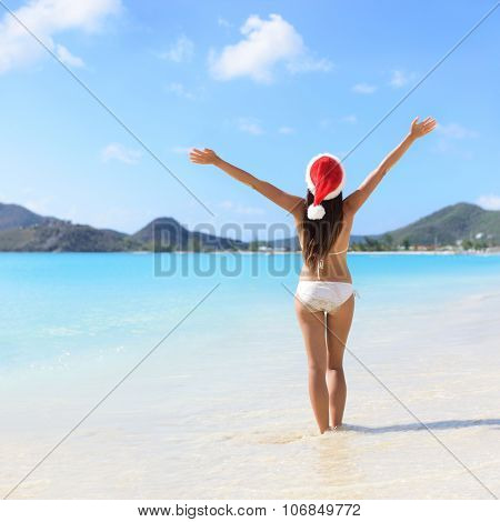 Woman standing in water with arms outstretched at beach. Rear view of female is wearing Santa hat and bikini. Carefree tourist is enjoying Christmas vacation on sunny day.