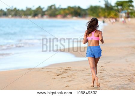 Young sporty woman running on beach. Full length rear view of determined female Runner in sports clothing. Jogger is exercising at sea shore during sunny day.