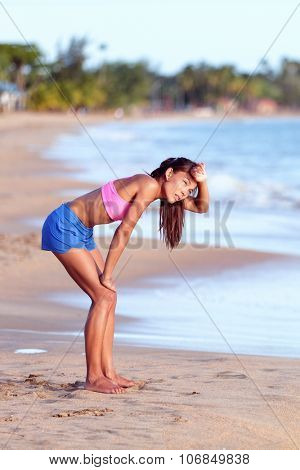 Tired runner bending on beach. Exhausted young woman is resting after running on sunny day. Full length side view of female in sportswear is looking away.