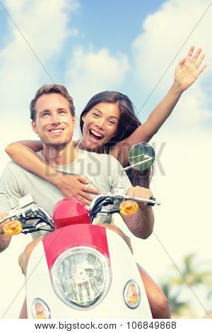 Happy young couple enjoying scooter ride against sky. Cheerful woman with arm raised screaming while man driving vehicle. Carefree male and female are enjoying their summer vacation.