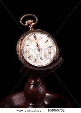 Ornament decorated old pocket watch on wooden stand showing 1 minute to n