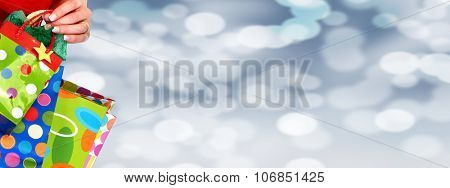 Woman hand with shopping bags over Christmas background.