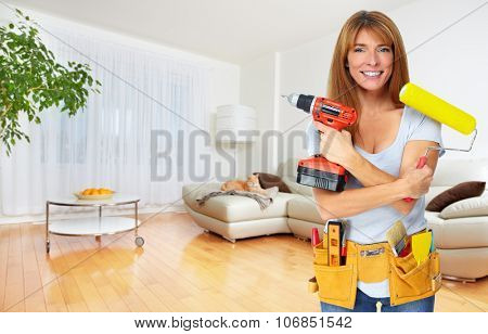 Beautiful woman with drill and paint roller. Renovation concept.