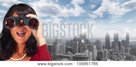 Business woman with binoculars over urban background.