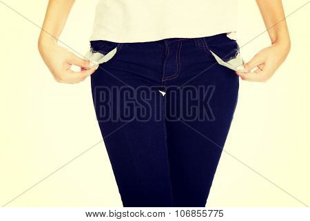 Young woman showing empty pockets.