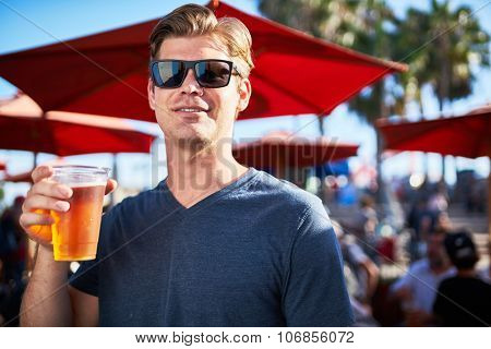 cool guy with cup of beer outside shot with selective focus