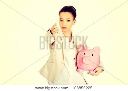 African businesswoman with piggybank and thumbs down.