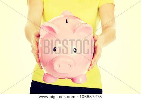 Woman's hands holding big piggybank.
