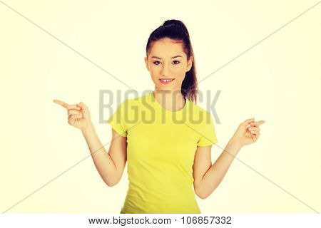 Young student woman pointing aside with both hands.
