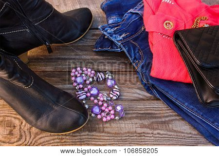 Women's autumn clothing and accessories: sweater, jeans, handbag, shoes, beads on wooden background.