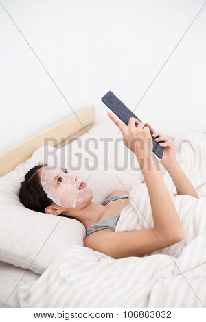Woman lying down with using facial mask adn tablet pc