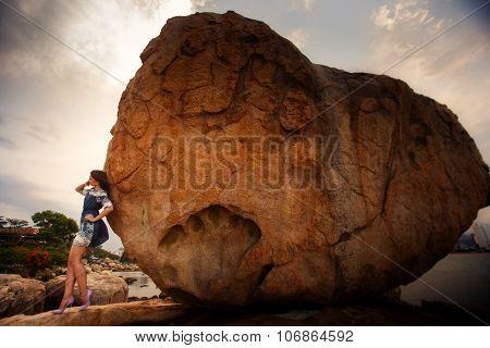 Brunette Girl In Short Frock High-heel Shoes Leans On Big Rock