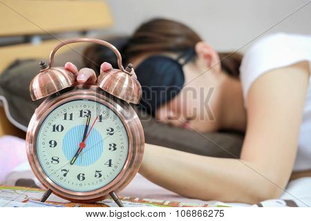 Young Women Sleepy In Bed With Blindfold And Closed Clock.
