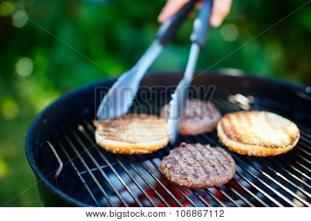 Grilling of fresh bun and burger meat cutlets for homemade burger cooking outdoors on summer day