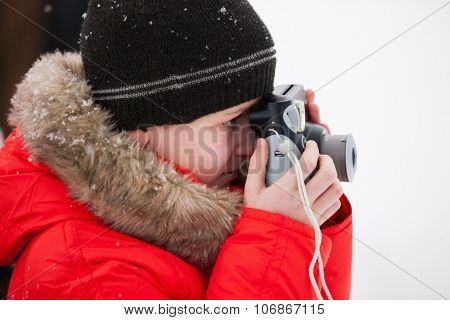 Cute boy in a red parka down jacket outdoors on beautiful winter snow day taking photos with small camera