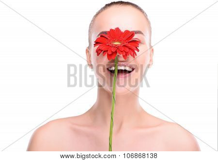 Cheerful beautiful woman hiding over red gerbera. Isolated on white background