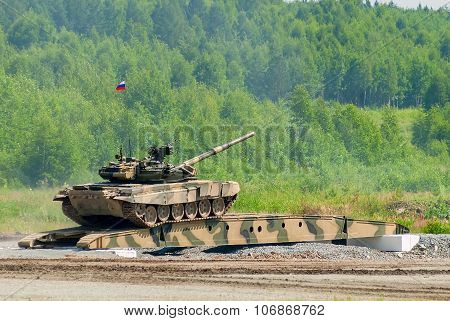 T-80 tank drives on bridge induced through obstacle