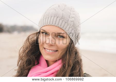 Portrait Of A Smiling Woman In A Gray Coat And A Pink Scarf In The Fall On The Beach