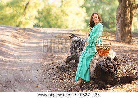 A Girl In A Long Dress Sat Down To Rest On A Fallen Tree
