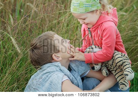 Cute Laughing Toddler Girl  Touching Her Sibling Brother Face At Summer Meadow Natural Background