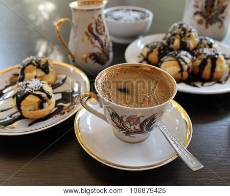 Profiteroles choux pastry, baked in the oven filling and custard poured chocolate and coffee
