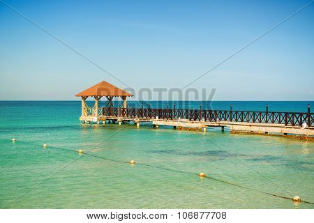 Dead Calm. Wooden Pier, Turquoise Sea, Blue Horizon And Clear Cloudless Sky.