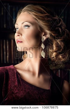 Beautiful young woman in  evening dress posing in vintage interior. Jewellery.  Fashion shot.