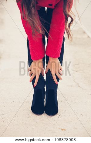 young woman on street in red coat touch her black high heels boots bent forward, closeup, selective focus
