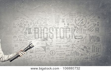 Hand holding glowing flashlight and business sketches at background