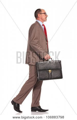 side view of a senior businessman holding suitcase and walking on white background