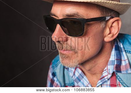 side view of a senior casual man's face wearing hat and sunglasses, looking away from the camera