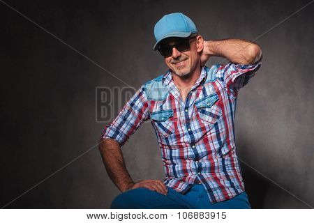 cool mature casual man in jeans clothes and trucker hat posing with hand behind his neck and smiles in studio