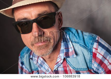 head and shoulders of a happy mature casual man wearing hat and sunglasses looking at the camera in studio