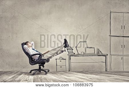 Smiling businessman sitting in chair with legs on table