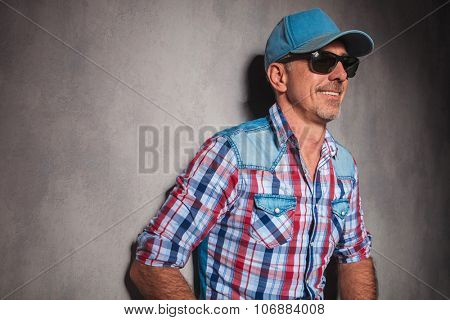 side view of a cool old guy in trucker hat laughing in studio