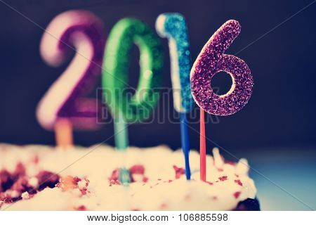 closeup of four glittering numbers of different colors forming the number 2016, as the new year, topping a cake