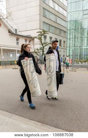 BADEN, SWITZERLAND. November 2nd, 2015. Workers carrying the new General Electric logos on large adhesive foils into the former Alstom thermal power headquarters.