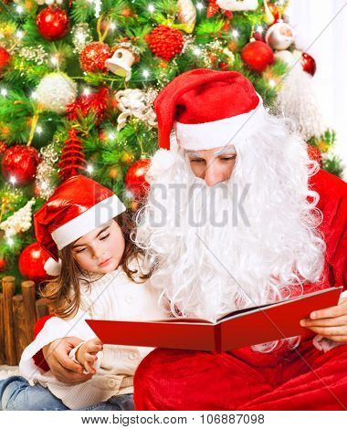 Cute little girl with Santa Claus sitting near Christmas tree and reading book, enjoying happy New Year eve at home