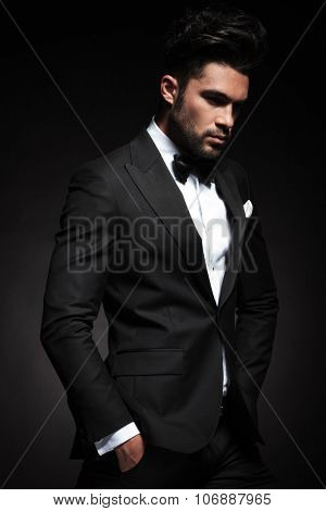 Side view picture of a elegant business man posing on black background with both hands in his pocket.