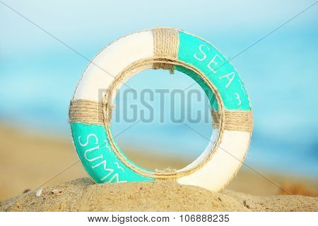Beautiful life buoy in the sand on unfocused sea background