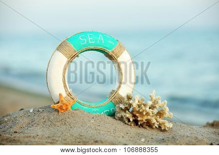 Beautiful life buoy in the sand with coral on unfocused sea background