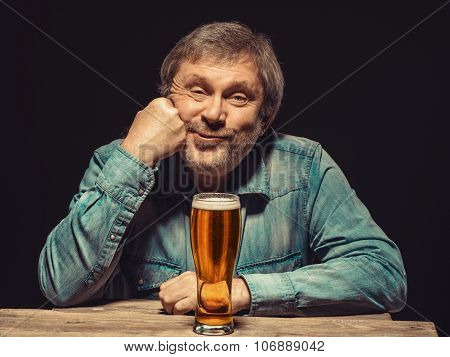 The satisfied man in denim shirt with glass of beer