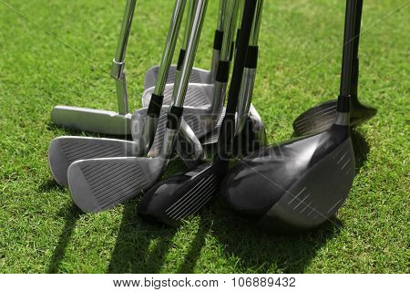 Different expensive golf clubs on green luxury golf course