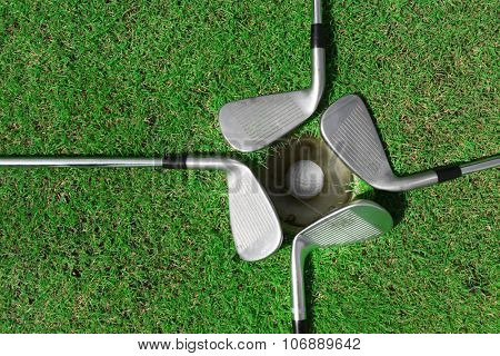 Golf ball in the cup with clubs around on luxury golf course, close up