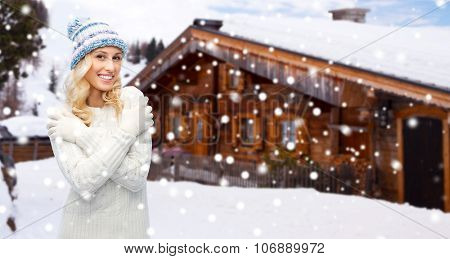 winter, vacation, christmas and people concept - smiling young woman in winter hat, sweater and gloves over wooden country house and snow background