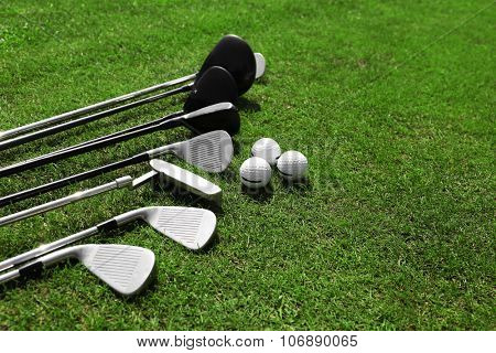 Different golf clubs in a row and balls on a green grass