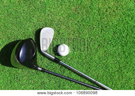 Golf clubs and ball on a green grass