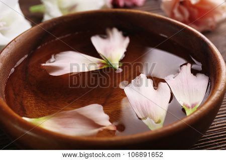 Pink rose petals in a bowl of water, close-up